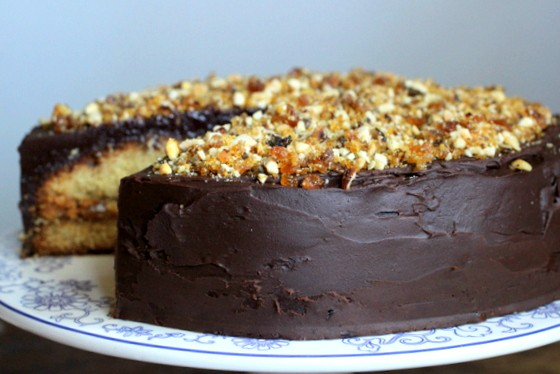 Chocolate praline covered yellow cake missing a slice on a cake stand