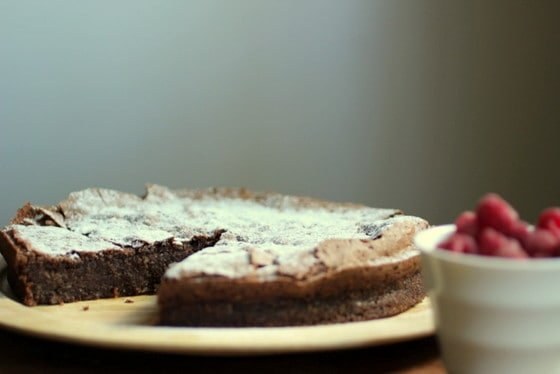 Chocolate Torte on wooden plate, white bowl with berries blurred beside