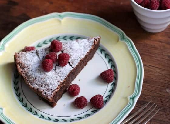 Slice of Chocolate Torte with fresh Raspberries on green yellow plate