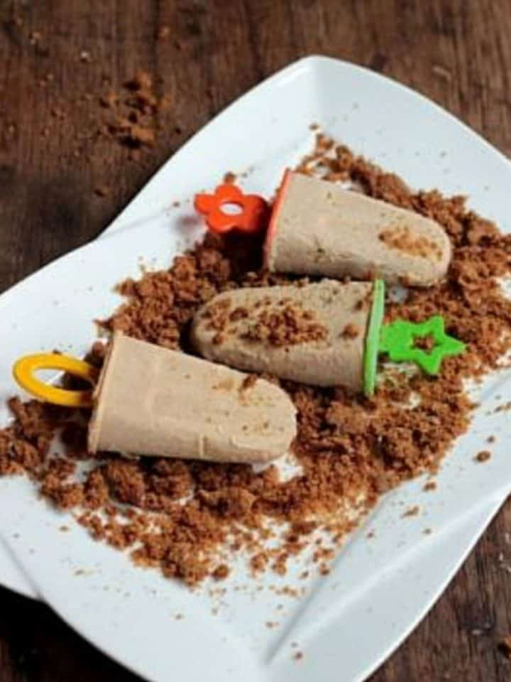 Three cinnamon popsicles on white plate on wooden tables