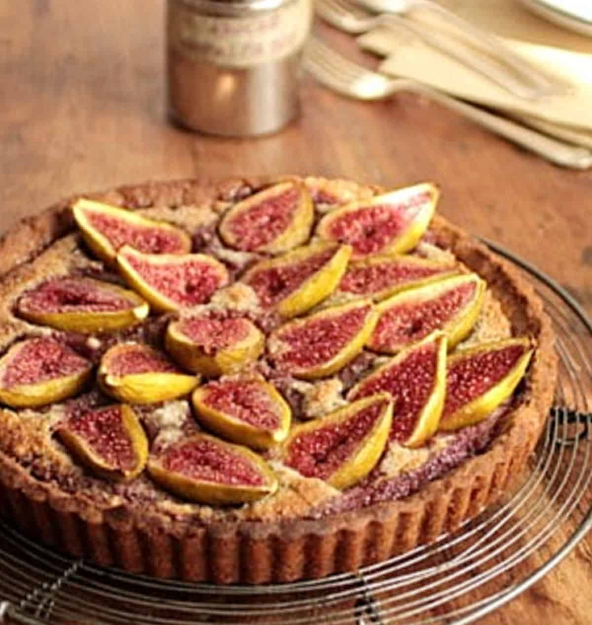 Whole fresh fig tart on wire rack on wooden table