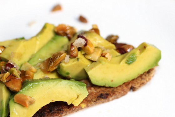 Partial close up view of avocado toast with pistachios on white surface