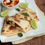 Chicken quesadillas triangles on white plate, wooden table