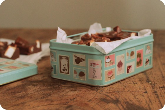 Vintage tin box with fudge pieces on a wooden table