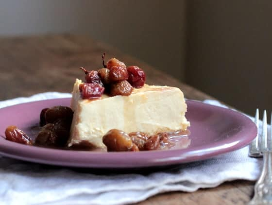 Slice of cheesecake on purple plate, roasted grapes