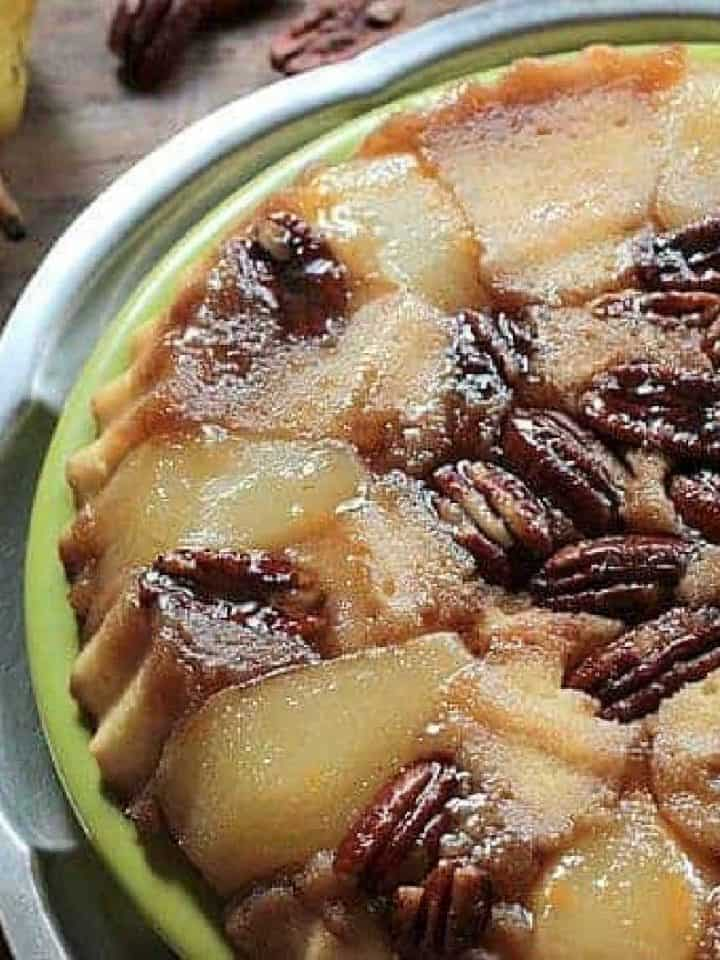 Partial pear upside down cake on green and silver platter; wooden table, whole pears, scattered pecans