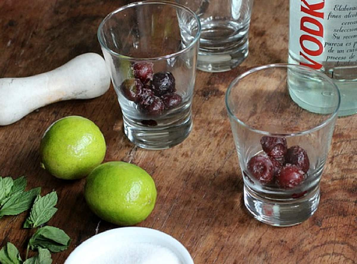 Glasses with cherries on wooden tables, limes, mint and muddler besides them