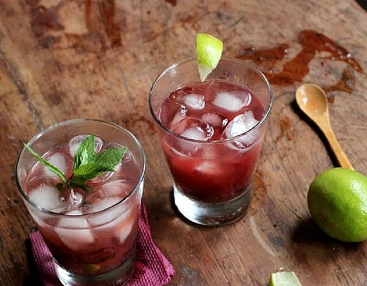 Top view of glasses with cherry cocktail and lime on wooden table