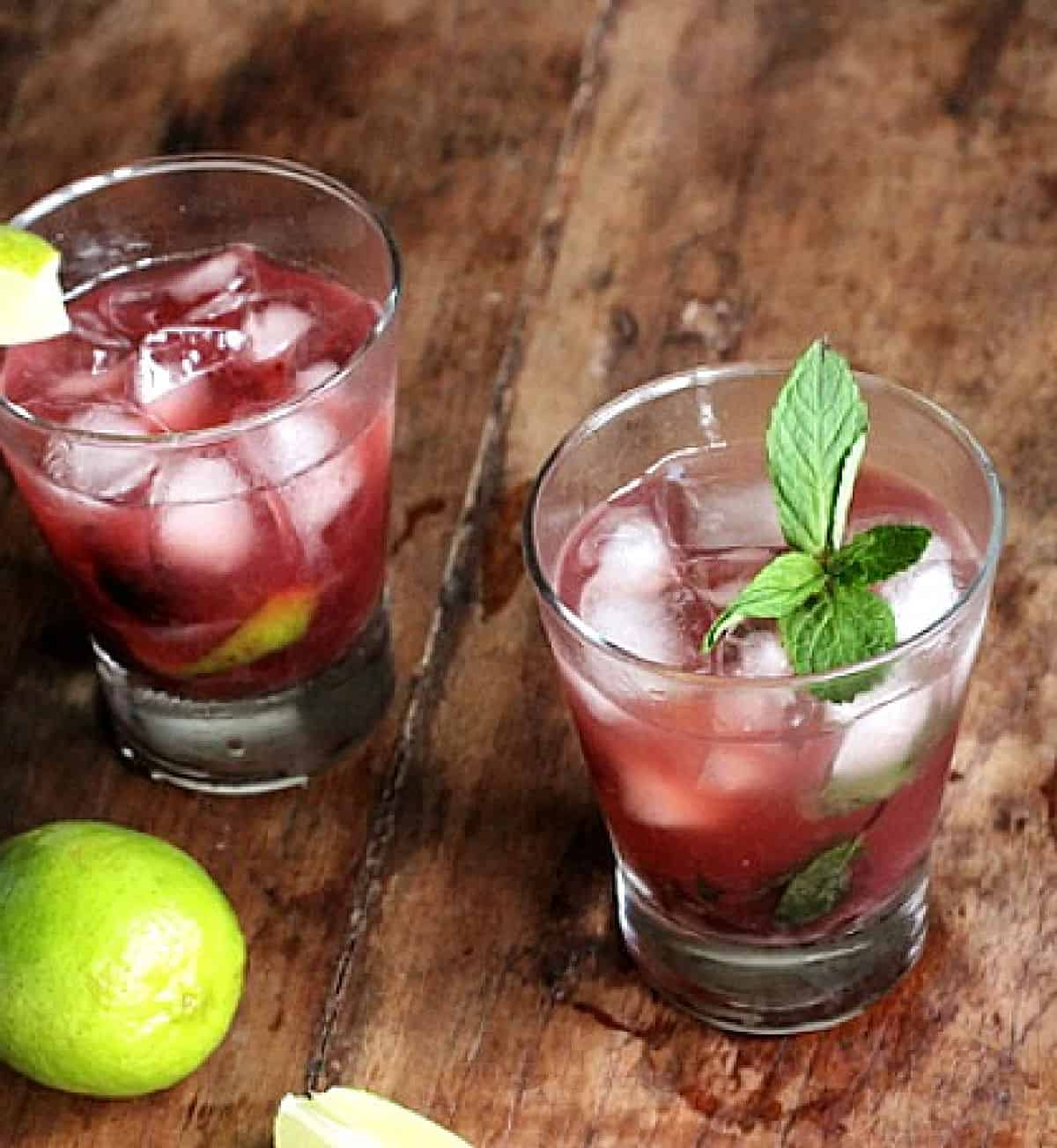 Wooden table with glasses of cherry cocktail, limes and mint sprigs