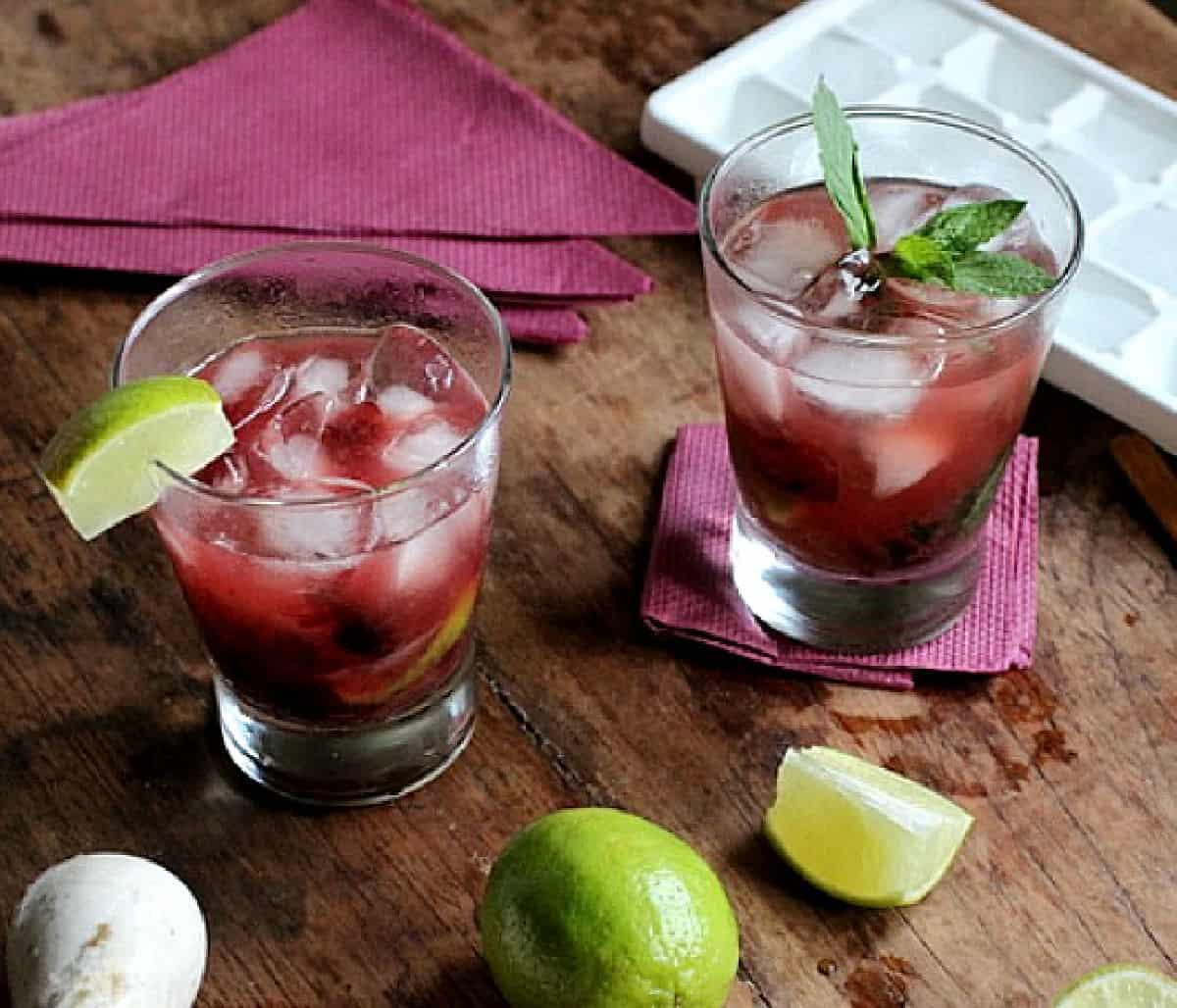 Two glasses with cherry cocktail on wooden table, limes, purple napkins