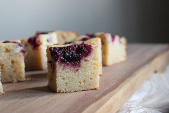 Squares of ricotta cake topped with berry jam on a wooden board