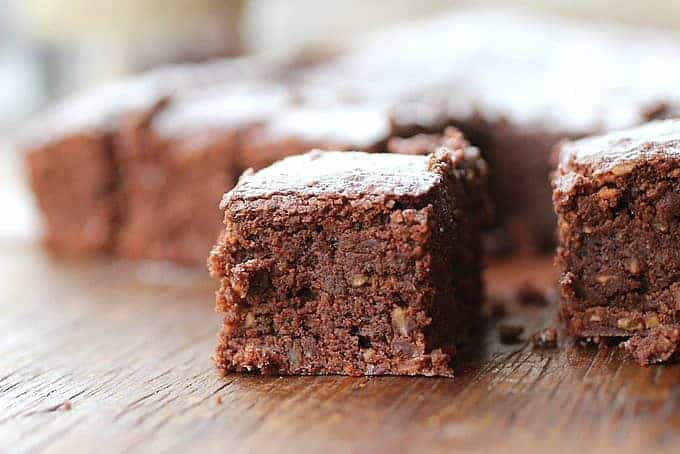 Close-up image of square of hazelnut brownie on wooden table