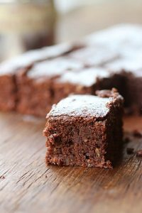 Close-up image of square of hazelnut brownie on wooden table. Rest of brownies in background