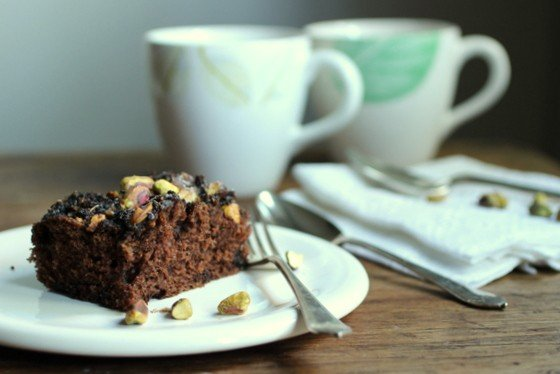 White plate with square of chocolate cake on wooden table, 2 mugs in background