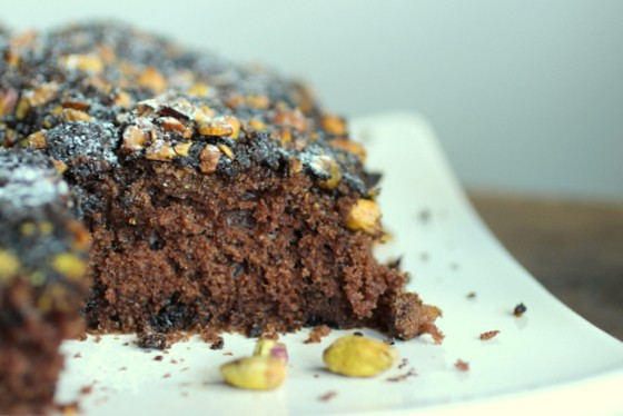 Close up of cut chocolate cake with pistachios on a white plate