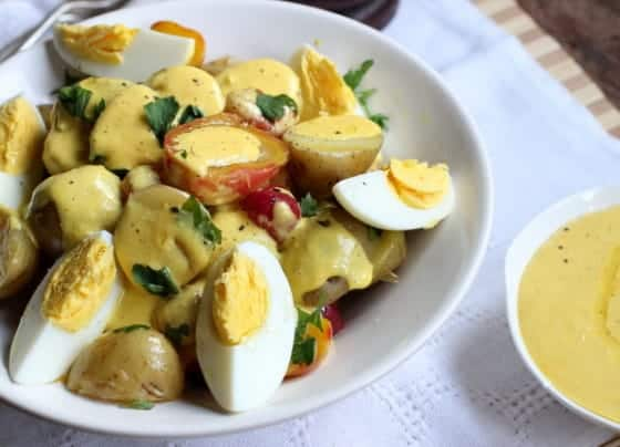 White bowl of Peruvian Potato Salad, dressing on the side