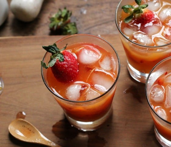 Glasses of Strawberry and Passion Fruit Caipirinha on wooden board