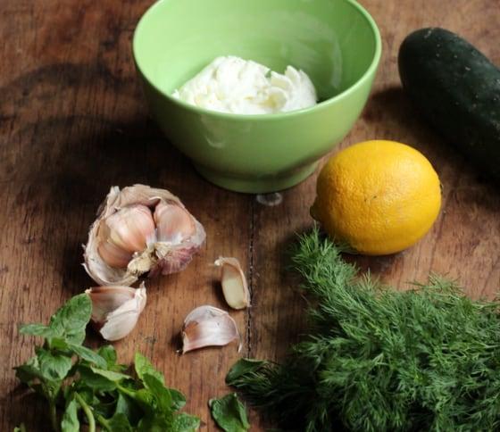 Ingredients on wooden table including garlic, herbs, lemon, bowl with yogurt