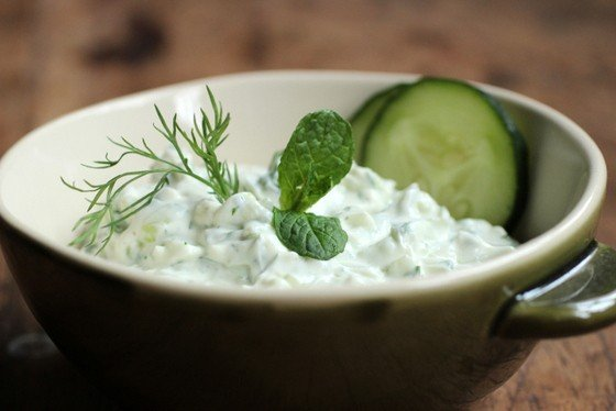 Close up of green bowl with yogurt cucumber sauce on wooden table