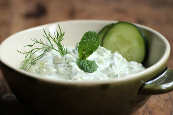 Green bowl with tzatziki, fresh herbs, cucumber slices, on wooden table