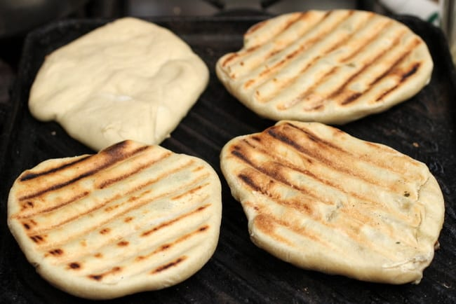 Grilling four naan breads on cast iron skillet