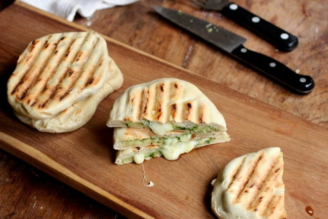 Wooden board with stacks of Mozzarella Pesto Grilled Naan Bread, knives