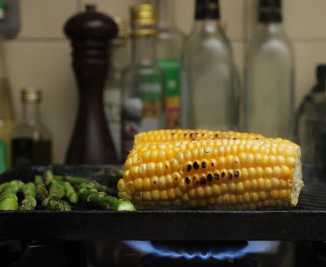 Charring corn and asparagus on black skillet over a flame; empty bottles and pepper mill in background