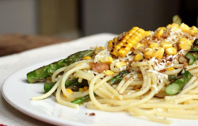 Side view of spaghetti with corn and asparagus on a white plate