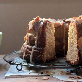 lemon almond bundt cake on wire rack, wooden table, green bowl, lemon