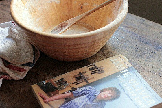 Wooden bowl with spoon on wooden table, a cookbook and kitchen towel