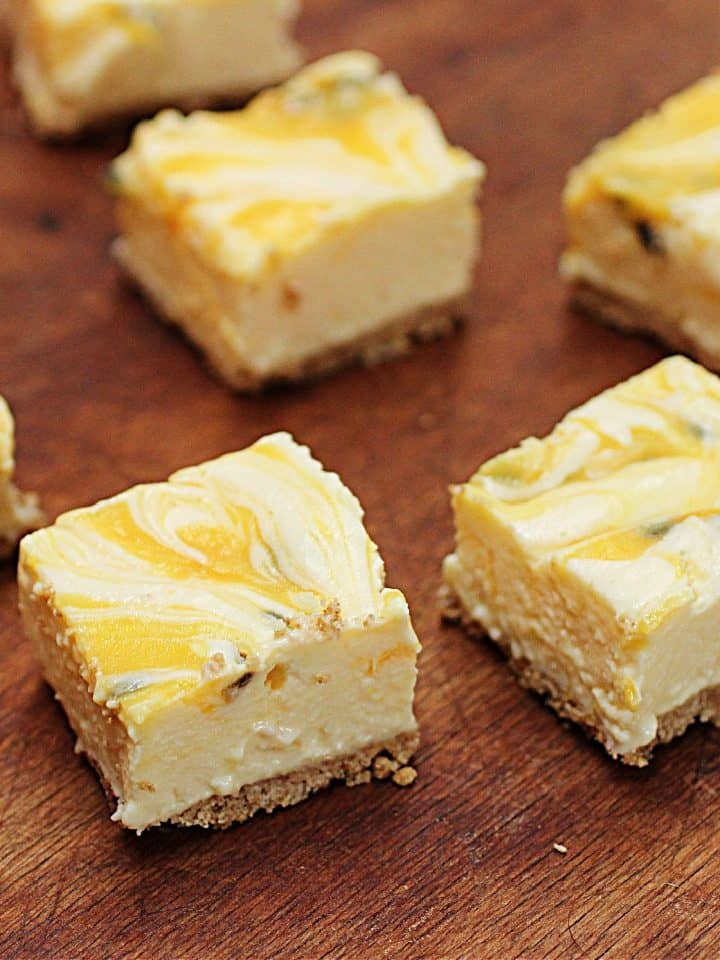 Squares of Passion fruit lemon no-bake cheesecake on wooden table