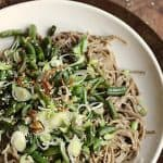 sesame soba noodles with green beans on white plate, wooden table