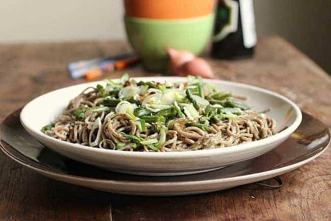 Sesame Asian Noodle Salad on white brown plates, bowls, shallots on wooden table