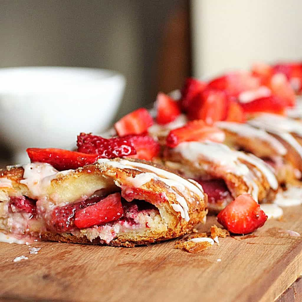 Strawberry danish braid on wooden board, white bowl in background, fresh strawberries on top