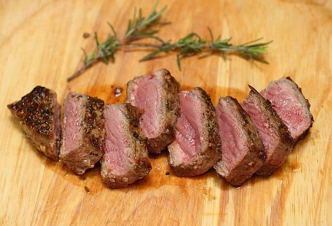 Cut pieces of Garlic Butter Steak, rosemary sprigs, wooden board