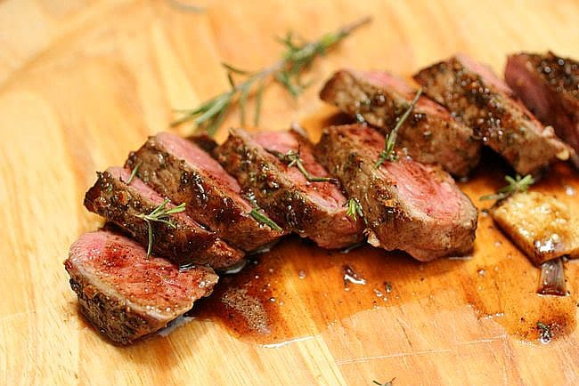 Cut pieces of Rosemary Garlic Butter Steak on wooden board