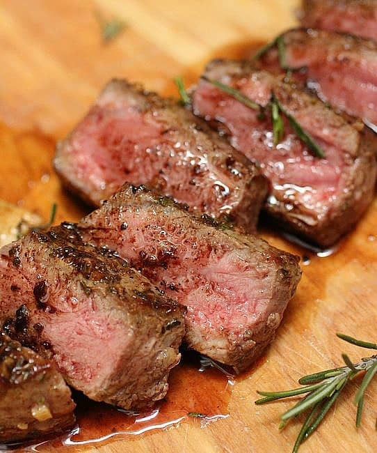 Close-up of cut Rosemary Garlic Butter Steak on wooden board