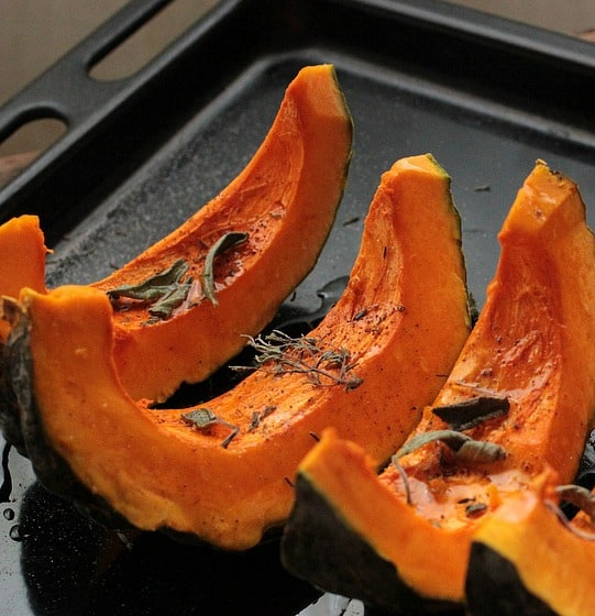 Raw Pumpkin wedges on baking tray with dried herbs