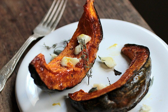 White plate with Roasted Pumpkin wedges on wooden table, silver fork