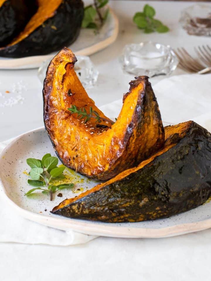 Roasted pumpkin wedges on white plate, white table, forks, fresh herbs
