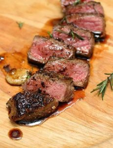 Cut slices of juicy Rosemary Garlic Butter Steak on wooden board