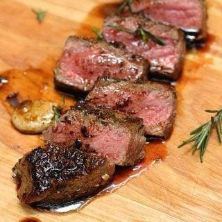 Cut slices of juicy Rosemary Garlic Butter Steak on wooden board