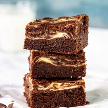 Stack of three cheesecake brownies on wooden table, green book besides