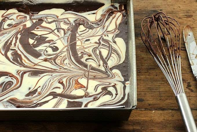 Square pan with cheesecake brownie batter on a wooden table, a whisk beside it