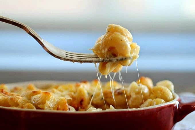 Silver Fork lifting cheesy mac and cheese from reddish dish