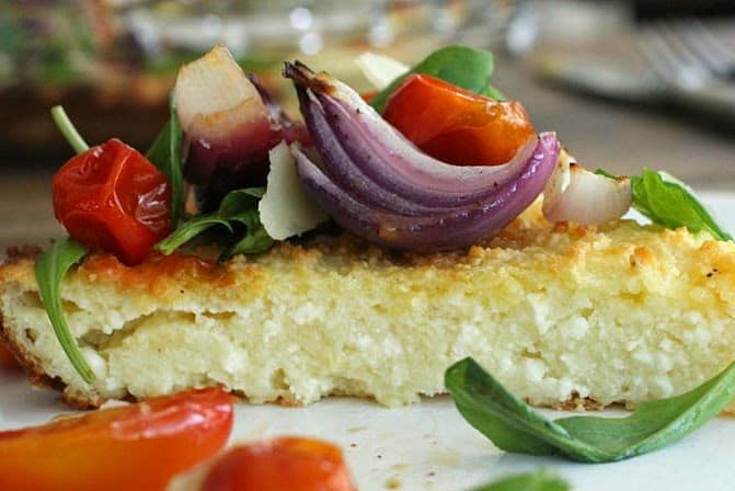 Close-up slice of baked ricotta with onion and tomatoes