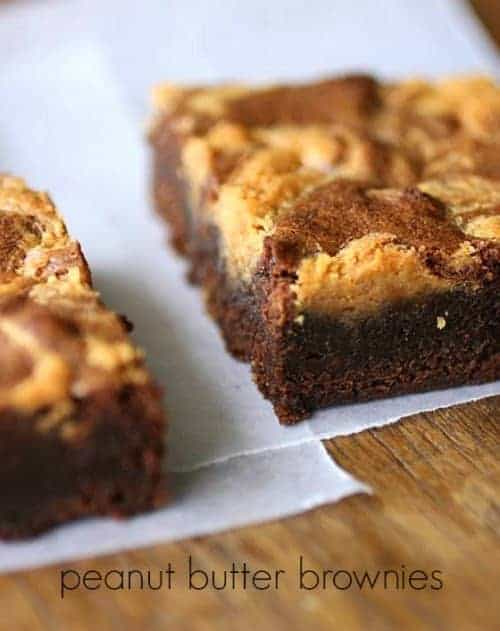 Partial view of squares of peanut butter swirled brownies on white paper on a wooden table