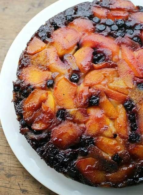 Partial view of Peach Upside Down cake on white plate on a wooden table