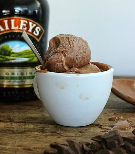 On a wooden table a white cup with scoops of chocolate ice cream, partial bottle of Baileys in background