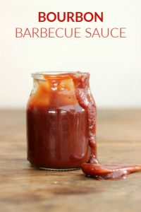 Smeared Jar of barbecue sauce on wooden table, spoon
